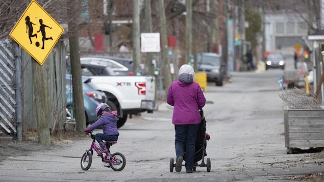 Une femme se promène avec de jeunes enfants dans une ruelle de Montréal.