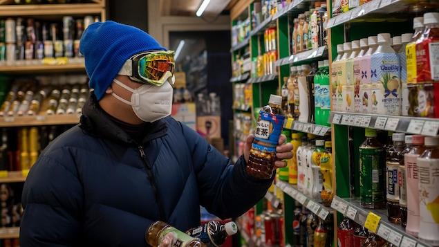 Un homme regarde une bouteille dans les allées muni de lunettes de ski et d'un masque.