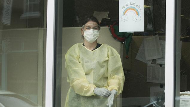 Eveline Gaillardetz est vêtue d'un habit de protection, d'un masque, de gants et de lunettes protectrices dans un local vitré.