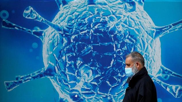 Un homme le visage recouvert d'un masque déambule à l'extérieur et passe devant une très grande illustration d'un coronavirus.