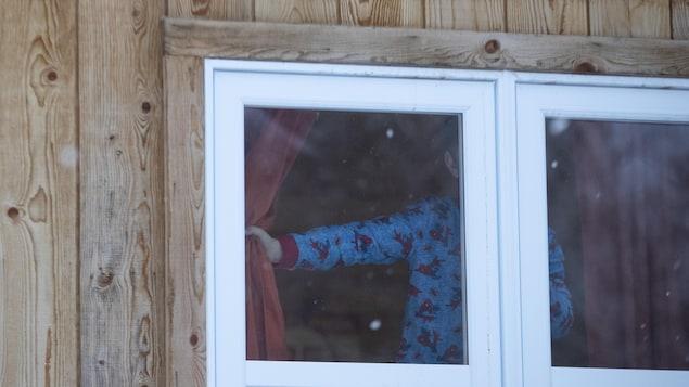Un enfant en pyjama regarde par la fenêtre.