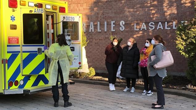 Quatre femmes regardent en direction d'une ambulance dont les portes sont entrain d'être fermées par le personnel médical.