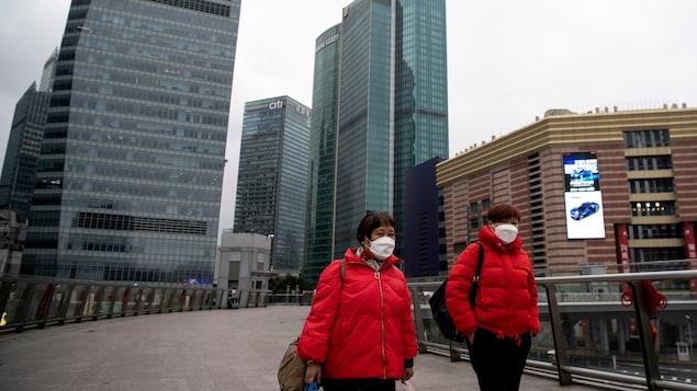 Deux femmes portant chacune un masque de protection marchent à l'extérieur, entourées de gratte-ciel.