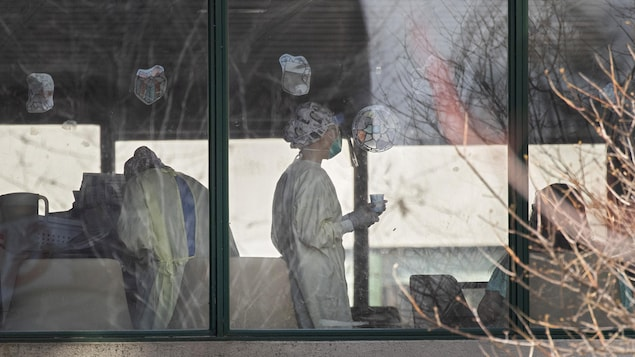 Des employés du CHSLD Herron vus depuis l'extérieur.