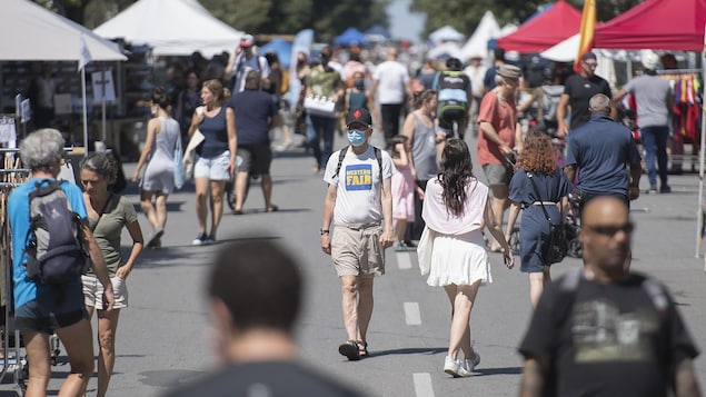 Un homme portant un masque marche sur le boulevard Saint-Laurent, à Montréal, au milieu d'une foule de piétons.
