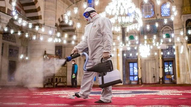Un homme en combinaison de protection pulvérise du désinfectant sur un tapis.