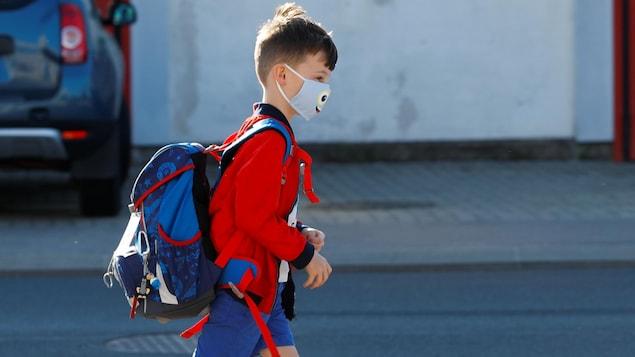 Un enfant porte un masque sur le visage. Il marche et a un sac à dos.