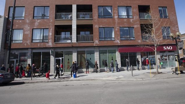 Longue file de personnes devant un magasin de la SAQ.