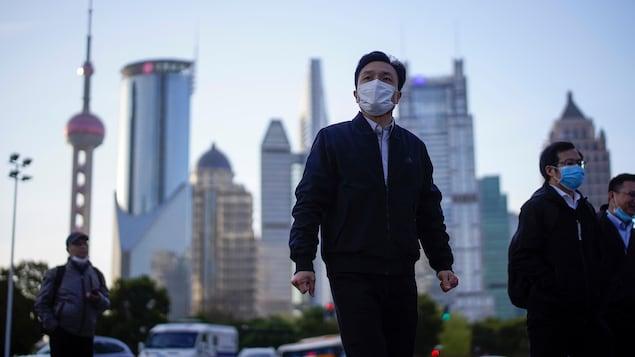 Des gens marchent dans le quartier financier de Shanghai.