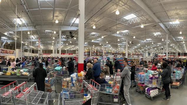 Un supermercado lleno de gente con los carros llenos.