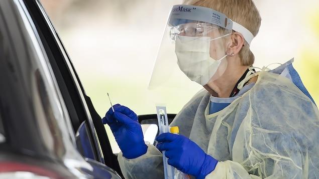 Une travailleuse de la santé tient une tige de test à côté d'un véhicule.