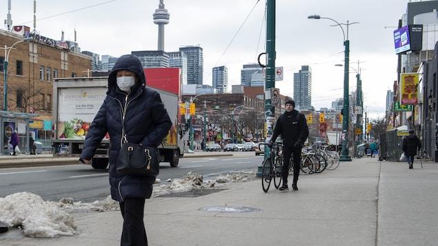 Des passants déambulent sur une rue dans un décor urbain.