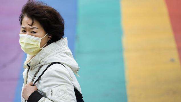 Une femme portant un masque dans la rue à Toronto.