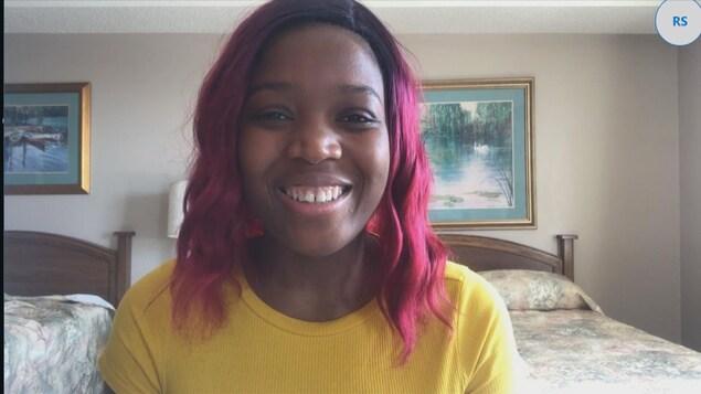 Une femme sourit dans une chambre d'hôtel.