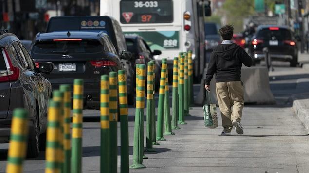 Un homme marche dans une voie réservée, séparée de la circulation par des piquets verts et jaunes.