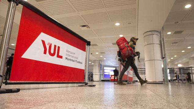Un homme marche dans l'aéroport Montréal-Trudeau avec un immense sac-à-dos sur son épaule droite.