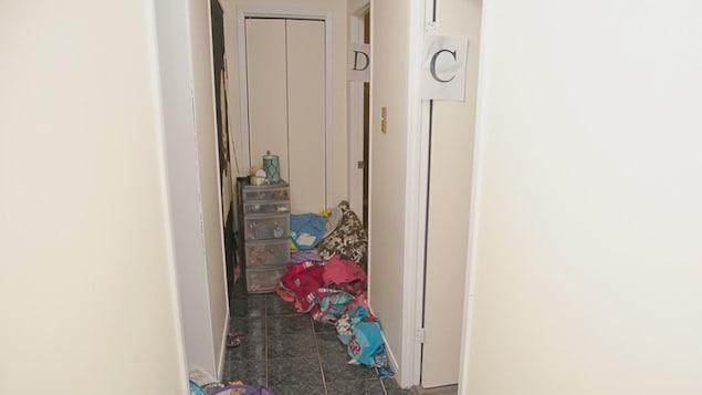 Un corridor avec des objets par terre et un classeur au fond.