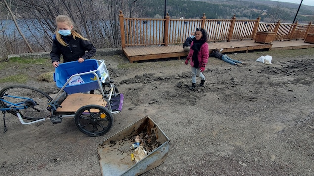 Deux jeunes filles ramassent des déchets devant un belvédère.
