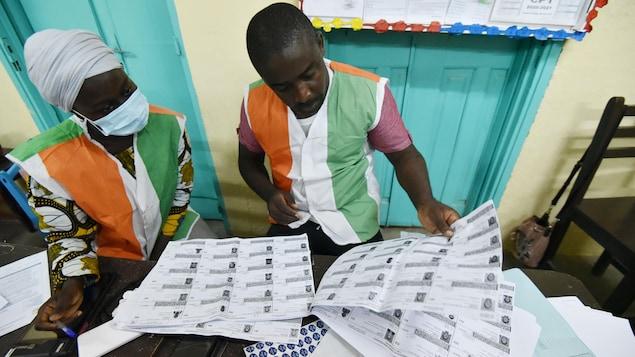 Une femme et un homme comptent le nombre d'électeurs sur des bulletins en papier.
