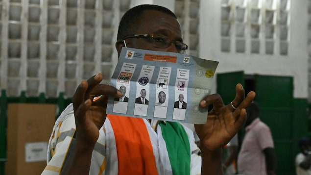 Un homme tient un bulletin de vote dans ses mains.
