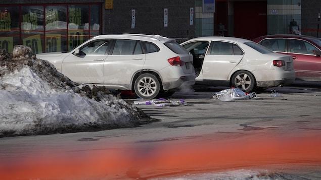 Dans un stationnement, une voiture a la porte grande ouverte du côté du conducteur.