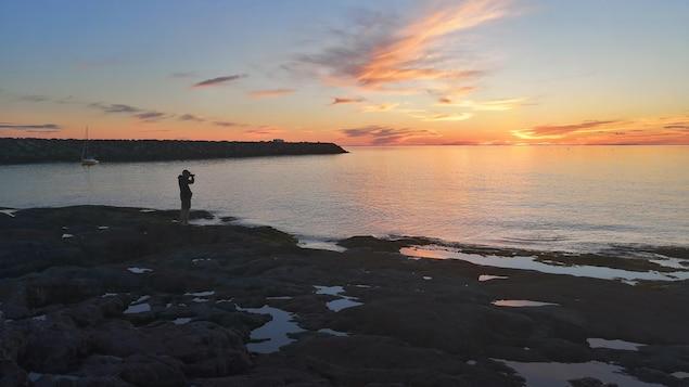 Un homme photographie le coucher du soleil à Rimouski.