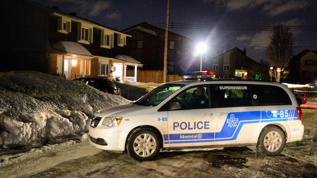 Une voiture du SPVM immobilisée dans une rue enneigée.
