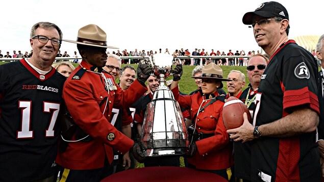 Le maire d'Ottawa, Jim Watson (à g.) et l'ancien joueur des Rough Riders d'Ottawa, Tony Gabriel (à dr.) avec la Coupe Grey.