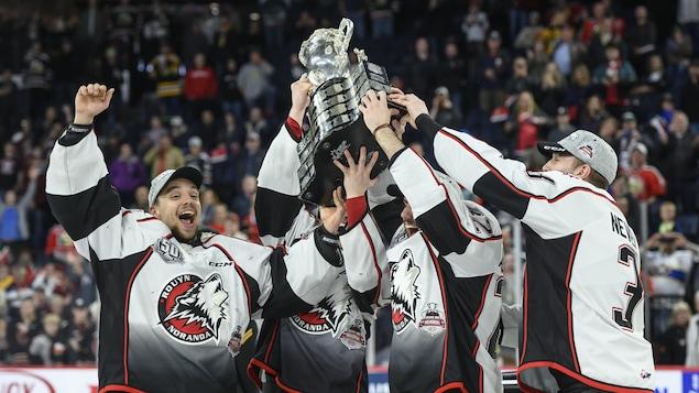 Des joueurs des Huskies soulèvent la Coupe Memorial sur la patinoire à Halifax le 26 mai 2019.