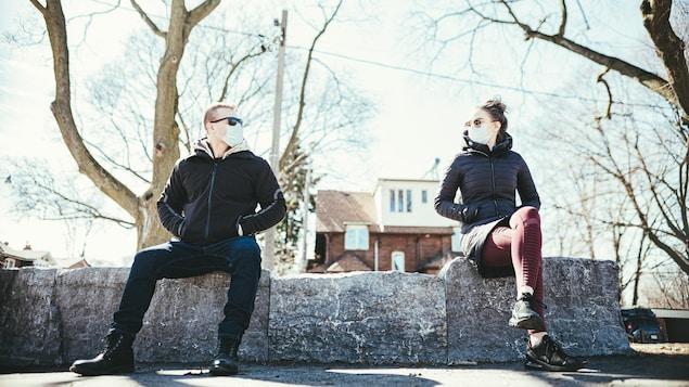 Un couple masqué assis dans un parc à un mètre de distance.