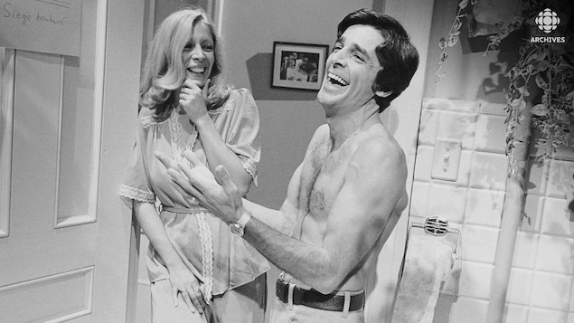 Description : Francine (Angèle Coutu) et Rémi Duval (Jean Besré), torse nu, rient en regardant une affichette placée sur la porte de la salle de bain.