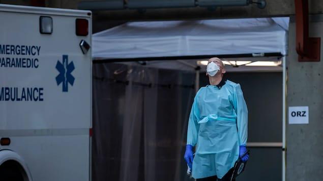Un travailleurs de la santé est à l'extérieur d'un hôpital.