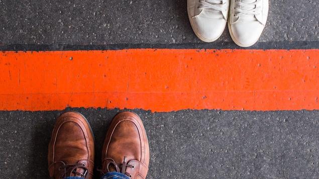 Les pieds d'une femme et ceux d'un homme séparés par une délimitation orange.