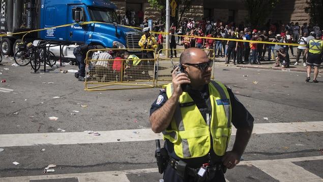 Un policier devant les secouristes penchés sur un blessé.