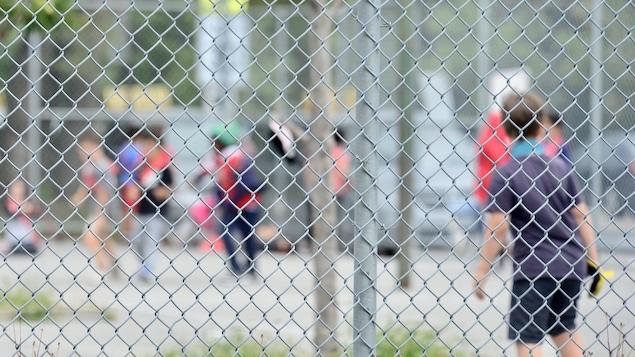 Des jeunes jouent dans une cour d'école.