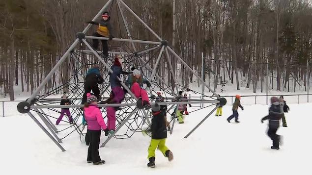 Des enfants en habit de neige jouent dans un module.
