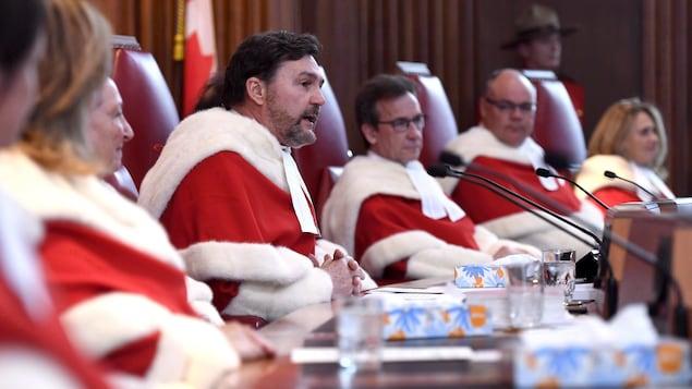 Sept juges de la Cour suprême siègent à une table.