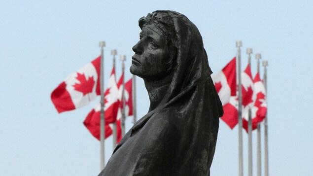 Une image de la statue Veritas devant l'édifice de la Cour suprême du Canada. L'oeuvre incarne la vérité.