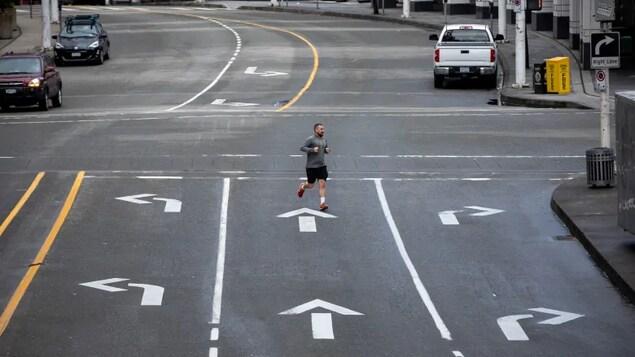 Un homme traverse une rue presque déserte.