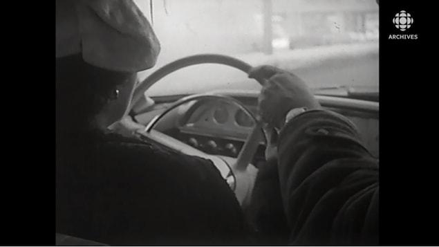 Femme vus de dos qui conduit et moniteur de conduite près d'elle avec une main sur le volant.
