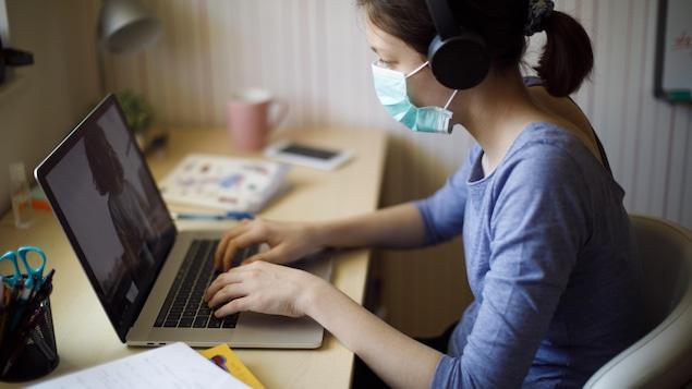 Une adolescente porte un masque de protection au visage et suit sur son ordinateur un cours en ligne à la maison.