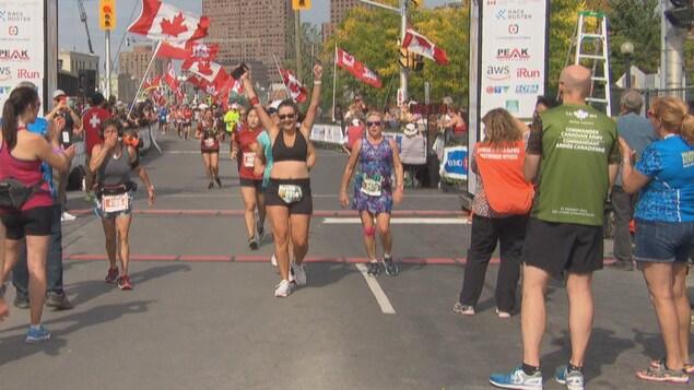 Une coureuse lève les bras en l'air, fière d'avoir achevé la course. Des drapeau du Canada flottent derrière elle.