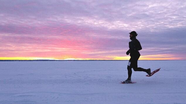 Un coureur en raquette sur le lac Saint-Jean.