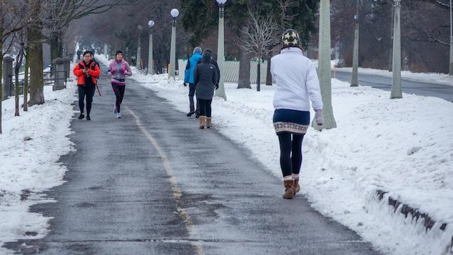 Des piétons et une coureuse sur une piste cyclable d'Ottawa.