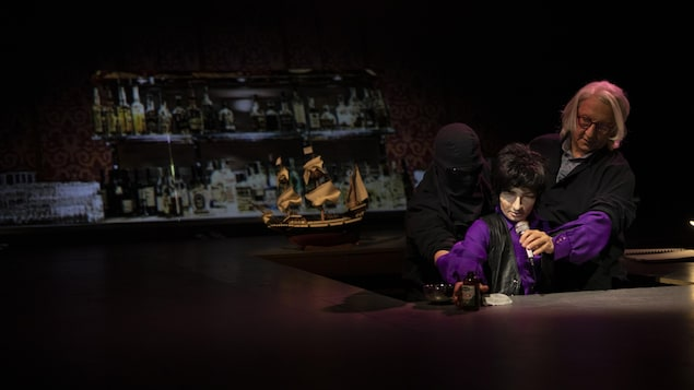 Un homme tient une marionnette dans un décor sombre.