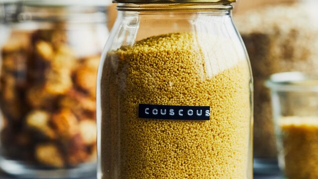 Pot transparent contenant du couscous sec.