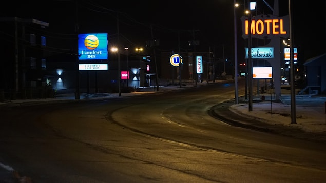 Un boulevard vide avec des enseignes lumineuses de motel à Rimouski.
