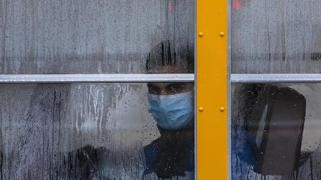 Un élève masqué dans un autobus.