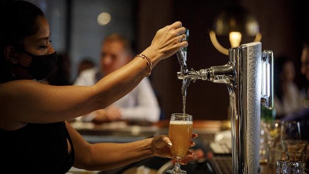 Une serveuse verse une bière dans un verre dans un bar.