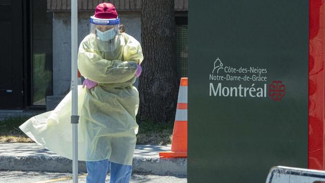 Une travailleuse de la santé, en équipement de protection, attend la tête baissée près de l'aréna.